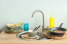 Pile Of Dirty Dishes In Kitchen