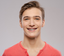 Smiling Teen Boy With Braces On His Teeth. Close-up Portrait Of A Beautiful Young Boy With Even Healthy Teeth.