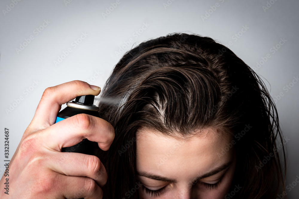 Fototapeta Woman applying dry spray shampoo on her dirty hair. Fast and easy way to keep your hair clean.