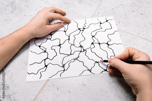 Man is drawing an abstract imaginary picture of curves by a black pencil in his hand Fototapete