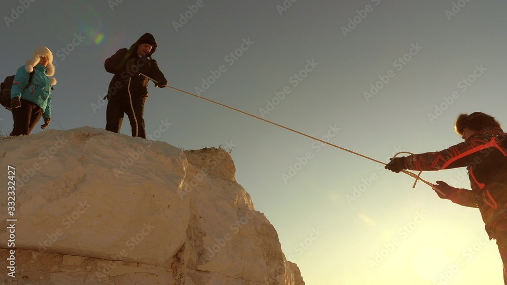 Fototapeta team of climbers climbs a mountain on rope. free woman helps a male traveler climb a mountain. teamwork of tourists. Travel and adventure in mountains at sunset. businessmen insure each other.