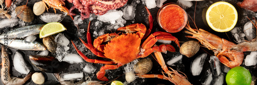 Crab with fish, shrimps, and caviar, overhead seafood panorama on a dark background