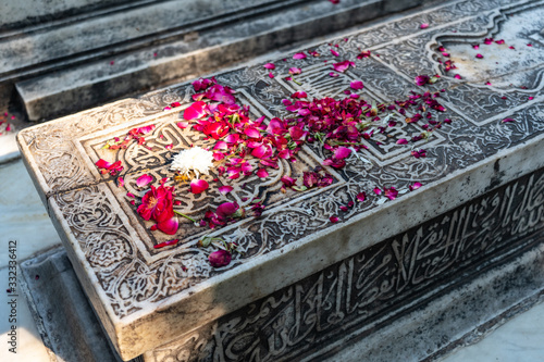 Valokuvatapetti ornamented old marble Muslim grave with flowers