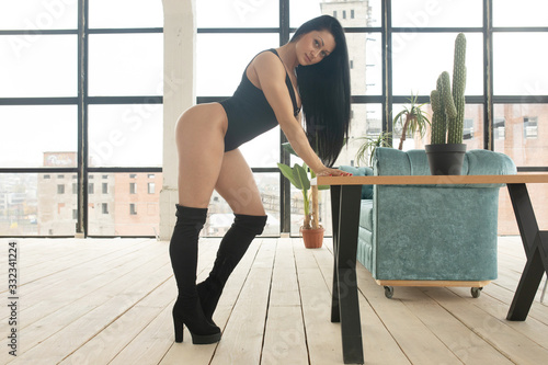 Young beautiful stunning girl with slim fit body and long hair standing in empty loft interior. Sensual young woman posing in sexy black lingerie.