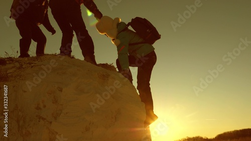 team of climbers climbs a mountain holding out helping hand to each other Canvas Print