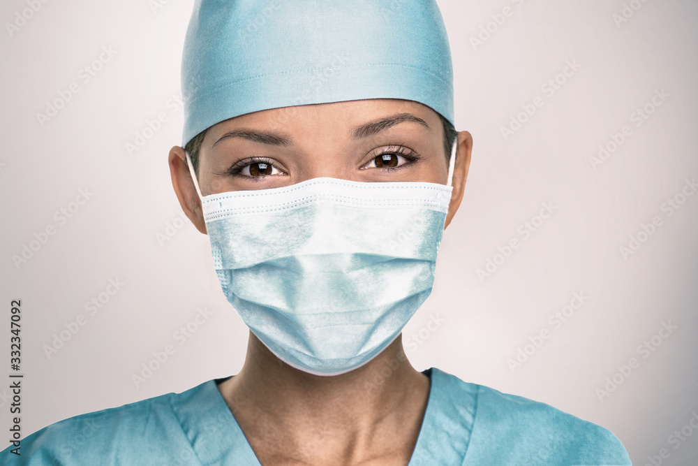 Fototapeta COVID-19 Coronavirus pandemic happy Asian doctor positive with hope wearing surgical mask and blue protective scrubs at hospital. Inspiring confidence in the future to solve the crisis.