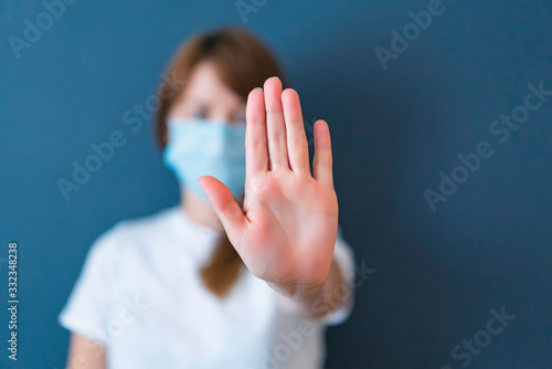 Obraz Coronavirus concept. Girl wearing mask for protection from disease and show stop hands gesture for stop corona virus outbreak. Global call to stay home. - fototapety do salonu