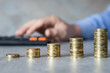 Oszczędności, męska dłoń licząca na kalkulatorze, monety poukładane w kolumny
