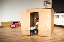 Child Looking Out Of A Cardboard Playhouse