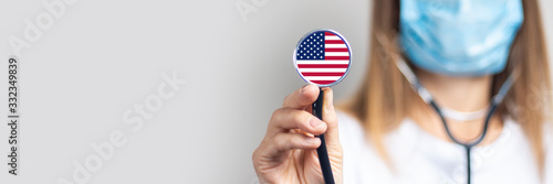 Obraz female doctor in a medical mask holds a stethoscope on a light background. Added flag of United States of America. Concept medicine, level of medicine, virus, epidemic. Baner - fototapety do salonu