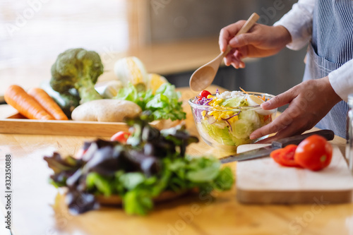 Closeup image of a female chef cooking and holding a bowl of fresh mixed vegetab Fotobehang