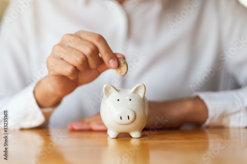 Fototapeta A woman putting coins into piggy bank for saving money concept obraz