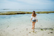 Outdoor summer portrait of young pretty woman looking to the ocean at tropical beach