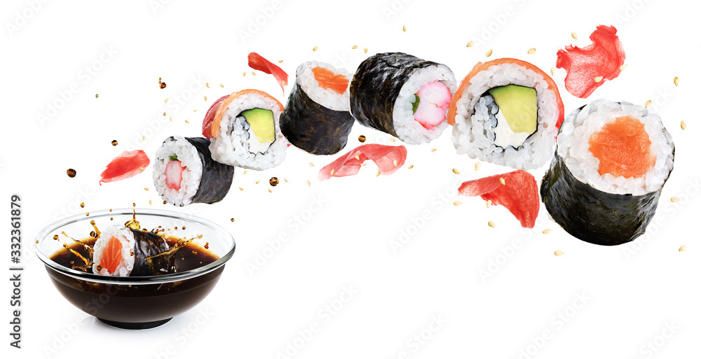 Fototapeta Concept of flying sushi with ingredients isolated on white background. Piece of sushi drops in a bowl with soy sauce.