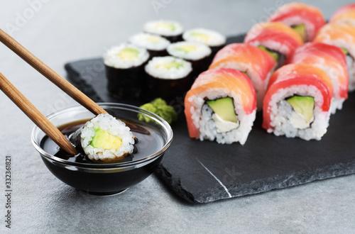 Fototapeta Sushi maki with avocado, sushi philadelphia, soy sauce and wasabi. Chopsticks taking portion of sushi roll. obraz