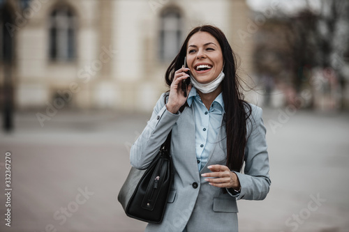 Photo Elegant woman walking on empty city street and wearing protective mask from dangerous flu or virus and using phone