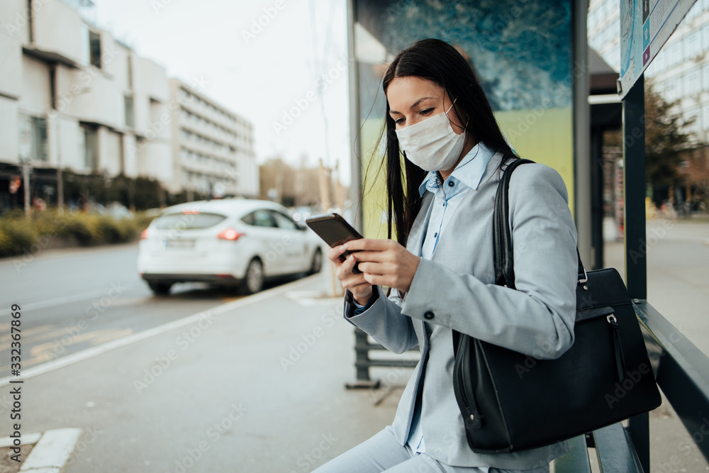 Fototapeta Elegant business woman with protective mask sitting alone on empty street and waiting for bus or taxi transport while using phone. Corona virus or Covid-19 lifestyle concept.