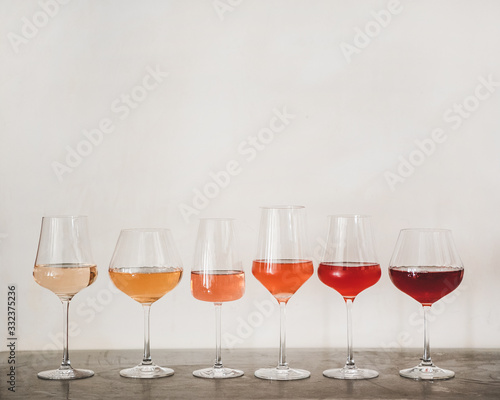 Fototapeta Various shades of Rose wine in stemmed glasses placed in line from light to dark colour on concrete table, white wall background behind, copy space. Wine bar, wine shop, wine tasting concept obraz