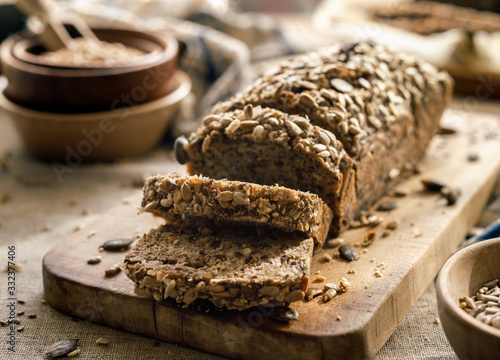Fototapeta Gluten-free homemade buckwheat bread with the addition of various seeds cut into slices on a wooden board close up obraz