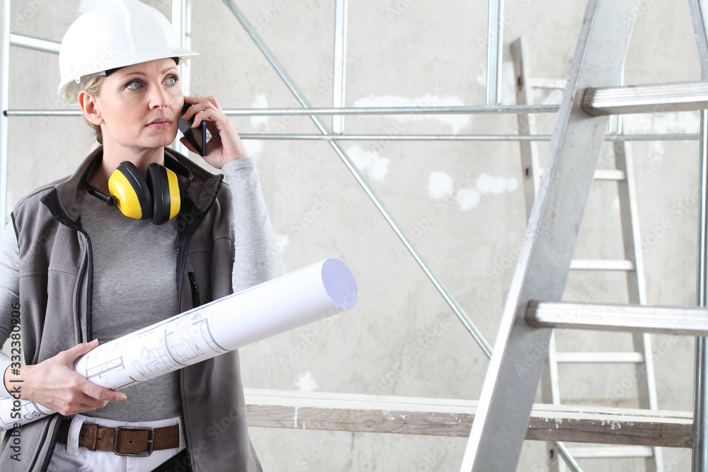 Fototapeta woman construction worker builder talking mobile phone and holding bluprint, wearing helmet and hearing protection headphones in building site indoors background