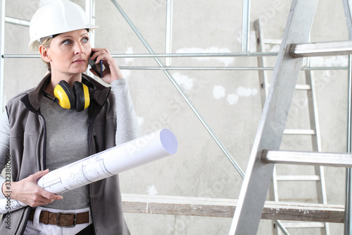 Fototapeta woman construction worker builder talking mobile phone and holding bluprint, wearing helmet and hearing protection headphones in building site indoors background obraz
