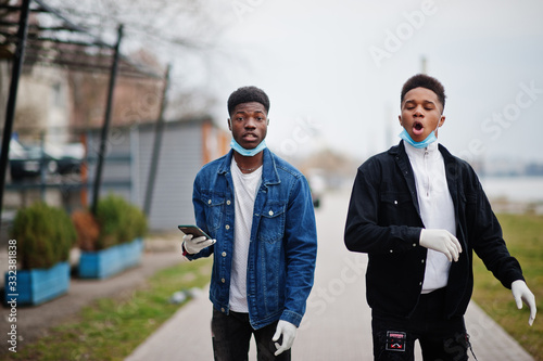 Two african teenagers friends at park wearing medical masks protect from infections and diseases coronavirus virus quarantine Wallpaper Mural