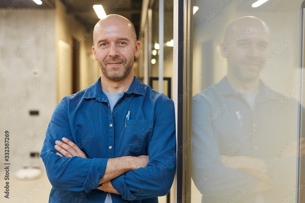 Fototapeta Waist up portrait of mature bald man smiling at camera while standing with arms crossed and posing confidently leaning against wall, copy space