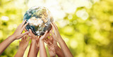 Group of children holding planet earth over defocused nature background with copy space