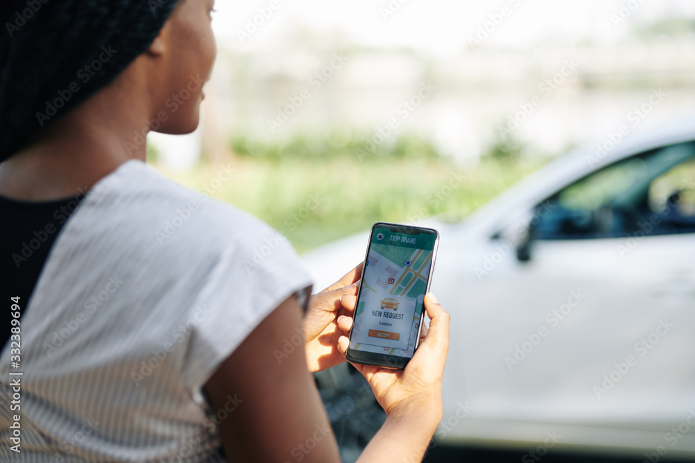 Fototapeta Female driver accepting new request in car sharing application, selective focus