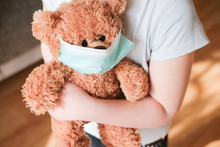 Little Girl Holding Teddy Bear In Medical Mask To Protect From Coronavirus.