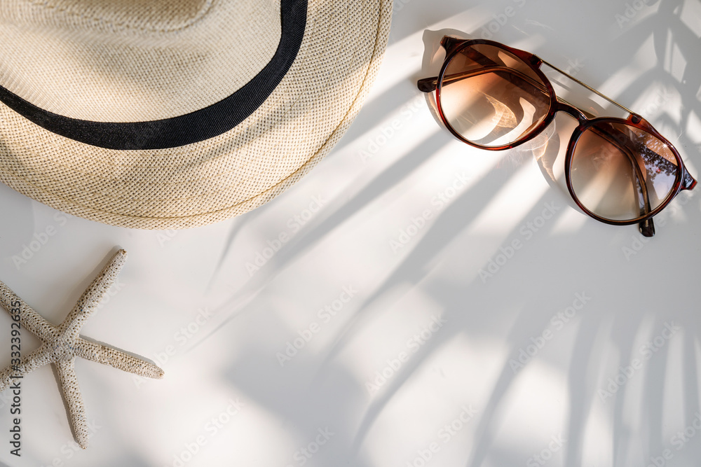 Fototapeta Travel accessories on the table with shadow of plam leave, Summer vacation concept