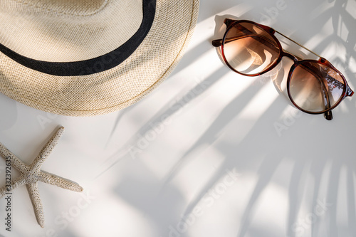 Obraz Travel accessories on the table with shadow of plam leave, Summer vacation concept - fototapety do salonu