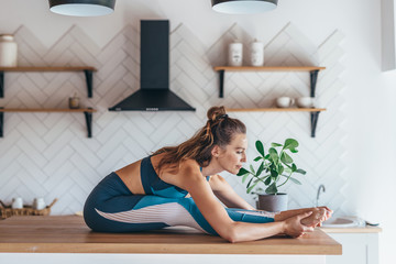 Woman leans forward stretches her back and legs