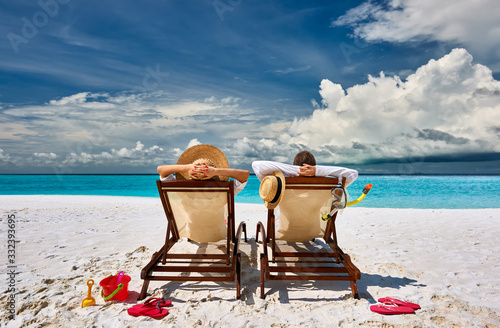Obraz Couple in sun beds on a tropical beach - fototapety do salonu