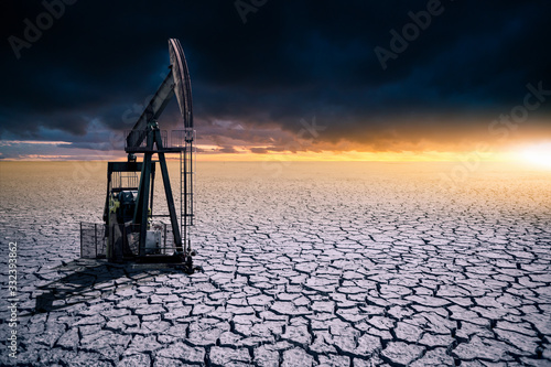 Fototapeta Oil rig in the desert on a background of a dramatic sky. Symbol of the crisis in the oil industry obraz