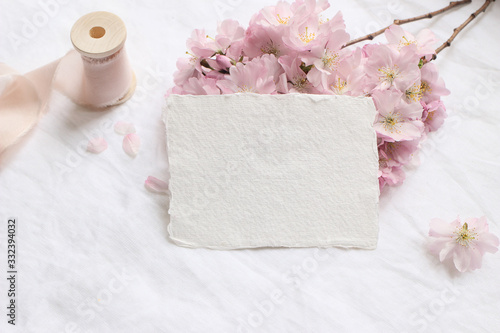 Fototapeta Wedding stationery mock-up scene. Blank greeting cards, envelope on linen tablecloth background with pink blossoming cherry tree branches and ribbon. Feminine still life composition. Flat lay,top view obraz