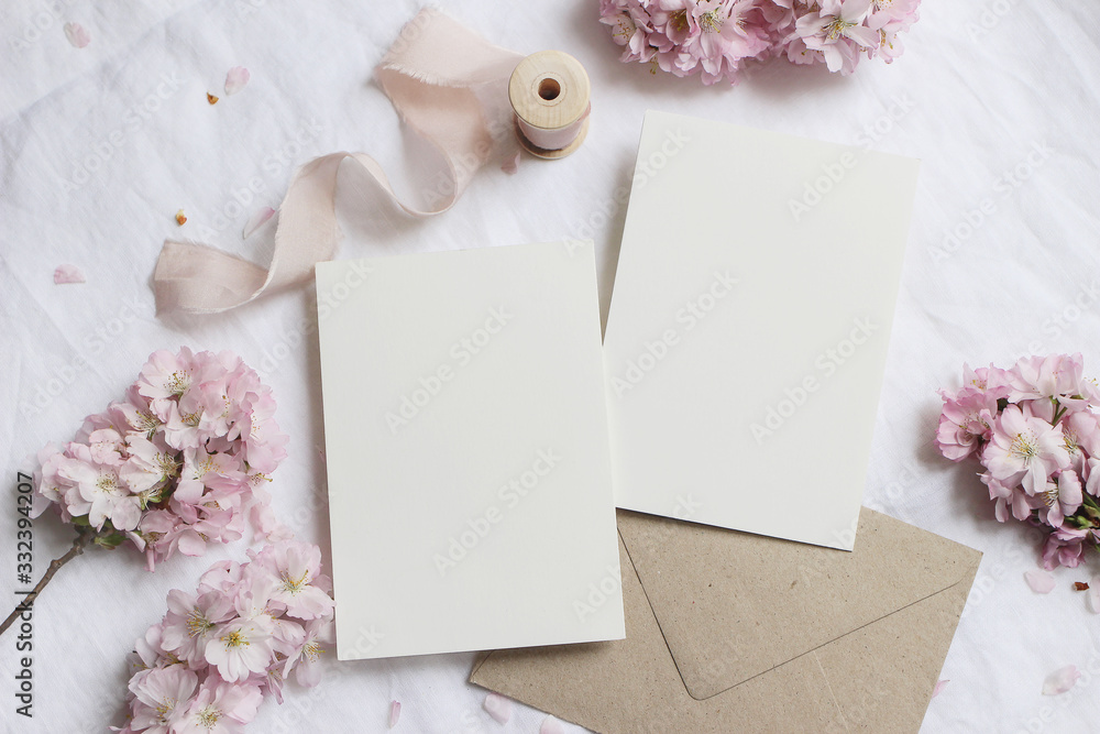 Fototapeta Wedding stationery mock-up scene. Blank greeting cards, envelope on linen tablecloth background with pink blossoming cherry tree branches and ribbon. Feminine still life composition. Flat lay,top view