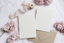 Wedding Stationery Mock-up Scene. Blank Greeting Cards, Envelope On Linen Tablecloth Background With Pink Blossoming Cherry Tree Branches And Ribbon. Feminine Still Life Composition. Flat Lay,top View