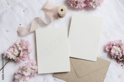 Obraz Wedding stationery mock-up scene. Blank greeting cards, envelope on linen tablecloth background with pink blossoming cherry tree branches and ribbon. Feminine still life composition. Flat lay,top view - fototapety do salonu