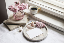 Spring Still Life Scene. Greeting Cards Mockups, Marble Tray, Cup Of Coffee, Old Books. Vintage Feminine Styled Photo. Floral Composition With Pink Sakura, Cherry Tree Blossoms On Table Near Window.