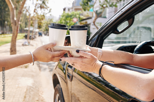 Female car driver buying two cups of take out coffee in drive through cafe