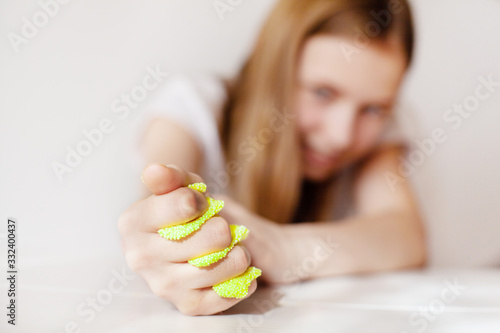 Obraz The young girl squeezes the yellow slime with her hand and looks at it with a smile. Toy for developing fine motor skills, the toy is from the slime - fototapety do salonu