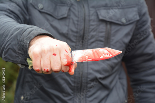 Photo A man is holding a knife with fake blood on knife and hand to illustrate crime, massacre or cruelty