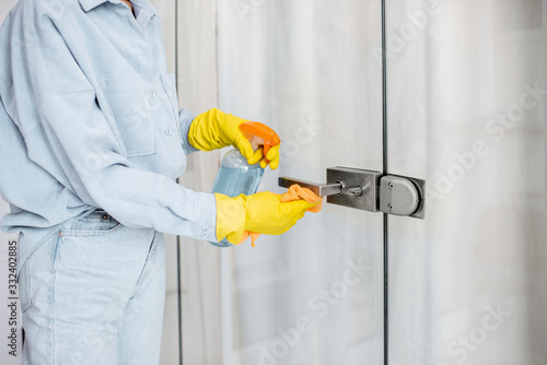 Fototapeta Woman in protective gloves disinfecting door handle while cleaning at home, close-up view on hands obraz
