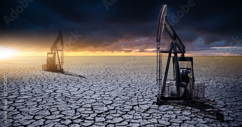 Obraz Oil rig in the desert on a background of a dramatic sky. Symbol of the crisis in the oil industry - fototapety do salonu