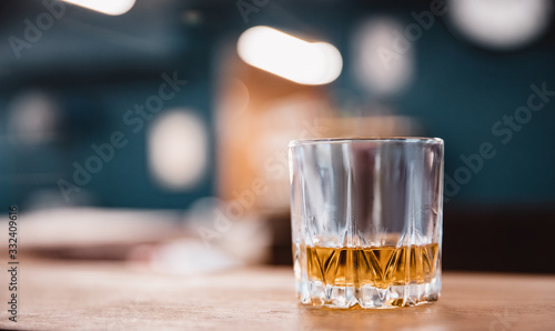 Photo Glass with edges of yellow brown whiskey stands on bar counter in barbershop