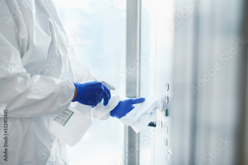 Obraz Technician disinfecting buttons of the elevator - fototapety do salonu