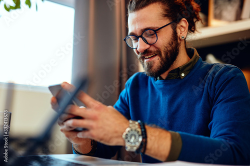 Fotografija Attractive caucasian bearded entrepreneur sitting in his office, using smart phone and taking a break from work