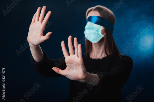a girl blindfolded, with a blue ribbon, looking for coronavirus medicine Canvas Print