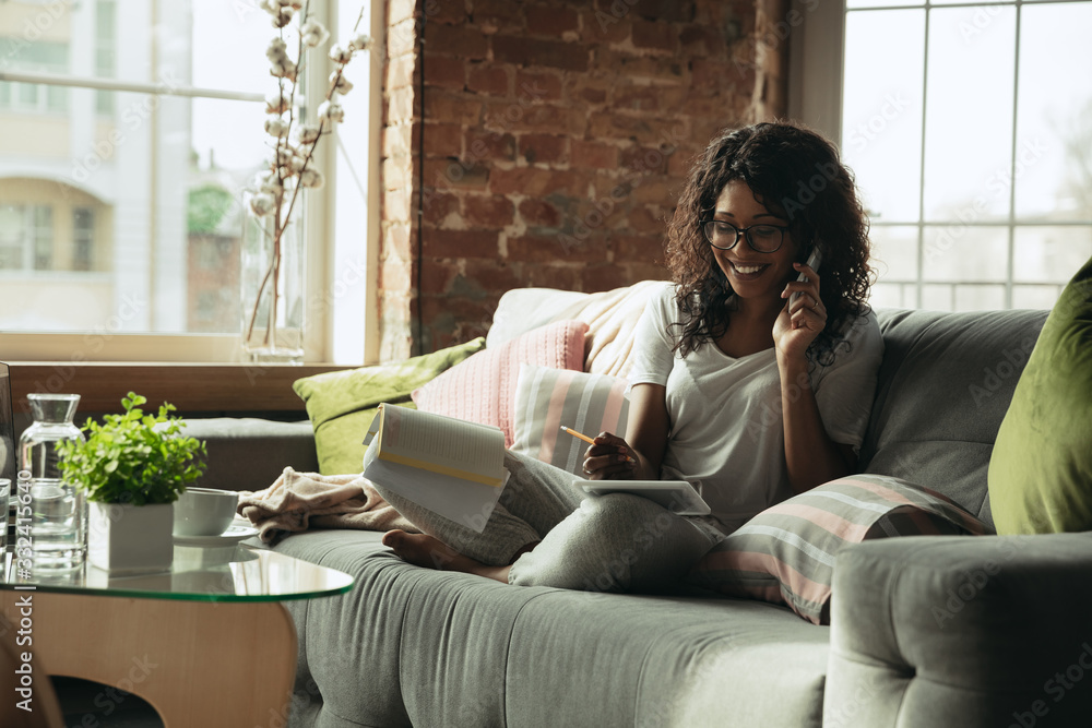 Fototapeta Talking on phone. Woman, freelancer during the work in home office while quarantine. Young female businesswoman staying at home, isolated. Using gadgets. Remote work, coronavirus spread prevention.